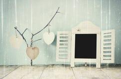 Dekoracyjnego chalkboard ramowi i drewniani wiszący serca nad drewnianym stołem przygotowywający dla teksta lub mockup retro filt Zdjęcia Royalty Free