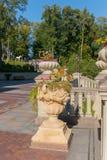 Dekoracyjnego kamienia flowerbeds, dekorujący z rzeźbami stiuk na tle zielenieją parkową strefę Zdjęcia Stock