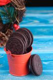 Dekoracyjny czerwony pail z czekoladowymi ciastkami na stole Zdjęcie Stock