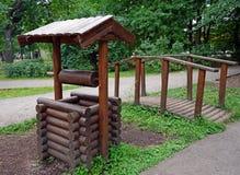 Dekoracyjny dobrze i mały most w miasto parku zdjęcia stock