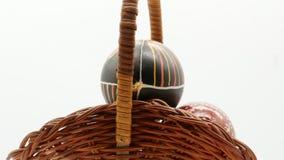 Dekoracyjny kosz z maluj?cymi Wielkanocnymi jajkami na bia?ym tle zbiory