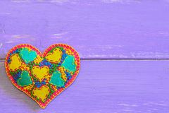 Dekoracyjny odczuwany serce dla walentynka dnia Upiększony kierowy ornament odizolowywający na purpurowym drewnianym tle z kopii  Zdjęcie Royalty Free