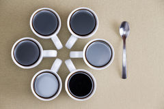 Dekoracyjny projekt kawowi kubki na beżu Zdjęcie Royalty Free