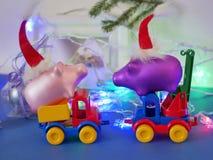 Dekoracyjny sezonowy skład zabawkarscy samochody, Bożenarodzeniowe zabawki, świnie w czerwieni czuł Santa kapelusze, Bożenarodzen zdjęcie royalty free