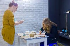 Dekoratörer för yrkesmässiga kvinnor som arbetar med kraft papper arkivfoto