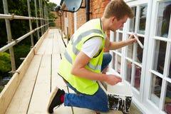 Dekorateur auf dem Baugerüst, das Außenhaus Windows malt Stockbild