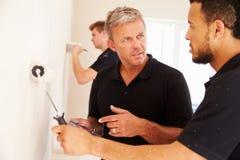Dekorateur, der den Kollegen malt einen Raum anweist stockfotos
