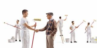 Dekorateur mit einem Rollenmaler, der Hände mit einer malenden Wand des Seniors und der Leute rüttelt lizenzfreies stockfoto