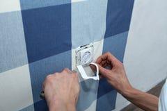 Dekorateur mit hängender Tapete des Skalpells über Wandsteckdose lizenzfreie stockfotos