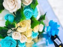 Dekoration der blauen und gelben Rosen auf Hochzeitstorte Lizenzfreie Stockfotos