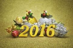 Dekoration des neuen Jahres 2016 mit Weihnachts-Verzierung auf Gold-backgro Lizenzfreie Stockfotografie