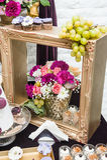 Dekoration mit den rosa, weißen und roten Blumen im goldenen Holzrahmen Hochzeitsdekor mit Trauben und Plätzchen Frische Rosen Stockbild