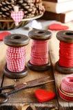 Dekoration mit hölzernen Spulen und roten Bändern Stockbilder