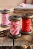 Dekoration mit hölzernen Spulen und roten Bändern Stockfotografie