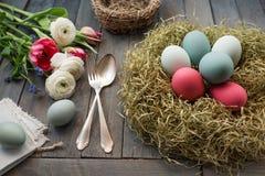 Dekoration mit Ostereiern in einem Nest und in den Blumen lizenzfreie stockbilder