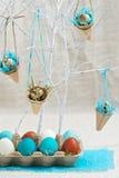 Dekoration von Ostereiern in den blauen Tönen Abbildung der roten Lilie Lizenzfreie Stockfotos