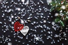 Dekorationen der frohen Weihnachten, Schneeflocken, weiße rote Herzen und grüner Weihnachtsbaum auf schwarzer hölzerner Hintergru Lizenzfreie Stockfotografie