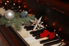 Dekorationen des neuen Jahres auf Klaviertastatur Weihnachtsniederlassung und -glocken stockfotos