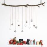 Dekorationen des neuen Jahres mit bereiften roten Beeren, Kerzen und Silberbällen auf Baumast Lizenzfreies Stockfoto