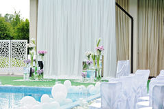 Dekorationen für die Hochzeitszeremonie durch das Pool mit blauem Wasser Stockfotos