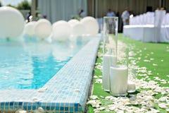 Dekorationen für die Hochzeitszeremonie durch das Pool mit blauem Wasser dekoration Lizenzfreie Stockbilder