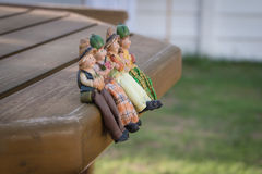 Dekorations-Puppen sitzen auf dem Holz Lizenzfreie Stockfotos