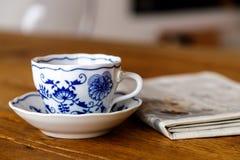 DekorationsKaffeetasse in der hölzernen Tabelle mit Zeitung Stockbild