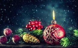 Dekorationskerze auf dem goldenen Hintergrund Weihnachtsbrennende Kerze mit Weihnachtsdekorationen in der schneebedeckten Atmosph Lizenzfreie Stockfotos