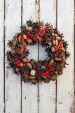 Dekorationsweihnachtskranz auf weißem rostigem hölzernes Brett backround, natürlicher Kranz, vertikal Lizenzfreie Stockfotografie