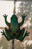 Dekorationszahl des grünen Frosches auf einer Tür in einem Garten Stockbild