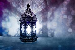 Dekorativ arabisk lykta med bränningstearinljuset som glöder på natten och blänker blåa bokehljus Festligt hälsningkort royaltyfria bilder