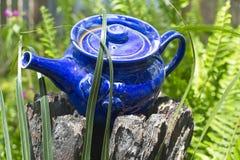 Dekorativ blå tekanna som används som den trädgårds- prydnaden på trädstubbe Royaltyfri Fotografi