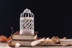 Dekorativ bur med stearinljusbränning på retro böcker på trätabellen arkivfoto