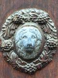 Dekorativ dörrplatta med lejonhuvudet i mitt och vinrankor omkring på historisk dörr i Banska Stiavnica, Slovakien Royaltyfria Bilder