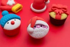 Dekorativ docka för jul av Santa Claus och snögubbe och närvarande ask och hatt och handske på rött Royaltyfri Bild