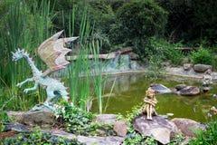 Dekorativ drake och felika statyer som sitter på kanten av dammet i b Royaltyfri Foto