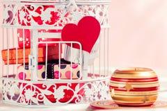 Dekorativ fågelbur, gåvor, hjärta och stearinljus Arkivfoton