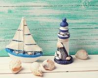 Dekorativ fyr, segelbåt och marin- objekt på trä royaltyfri foto