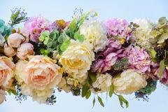 Dekorativ girland av konstgjorda blommor - rosor och vanliga hortensior Arkivbild