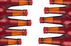 Dekorativ gräns av förseglade kalla röda ölölflaskor med vattendroppar som isoleras på vit bakgrund arkivbild