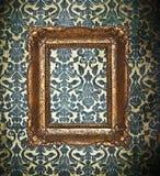 Dekorativ guld- ram på en damast tapet royaltyfria bilder