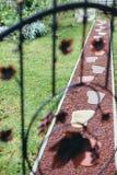 Dekorativ häftklammer med stora fotspår, trädgårdinre arkivbild