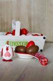 Dekorativ höna, chokladägg och rött påskägg i en stor sked Arkivfoto
