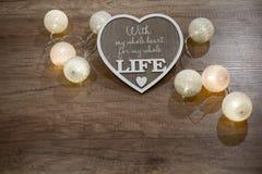 Dekorativ handgjord hjärta med text och ljus på trätabellen Arkivfoton
