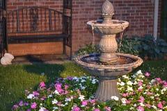 Dekorativ hem- vattenspringbrunn i en säng av blommor Royaltyfri Bild