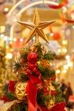 Dekorativ jul - stjärna på överkanten av en julgran med en härlig bokehbakgrund arkivfoto