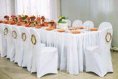 Dekorativ krans på vita stolar Stolar och tabell som täckas med Royaltyfri Fotografi