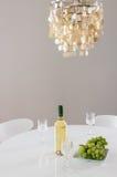 Dekorativ ljuskrona och flaska av vin på tabellen Arkivfoton