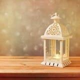 Dekorativ lykta med den glödande stearinljuset på trätabellen med kopieringsutrymme fira santa för modern för hattar för berömjul Arkivbild