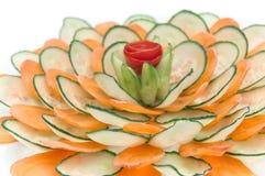 dekorativ presentation med morötter och gurkor I arkivfoto